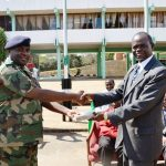 Mr Kamkwamba, Board Chairperson presenting the Bibles to Col. Saenda