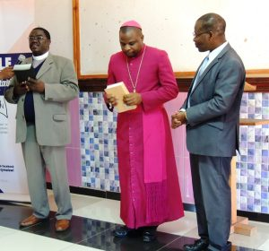 Rev Dr L Nyondo and Bishop Magangani receiving the Bibles on behalf of the church from Mr Clapperton Mayuni, BSM Executive Director